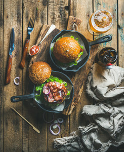 Beef burgers in cast iron pans and glass of beer