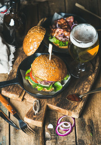 Beef burgers with crispy bacon  fresh vegetables and wheat beer