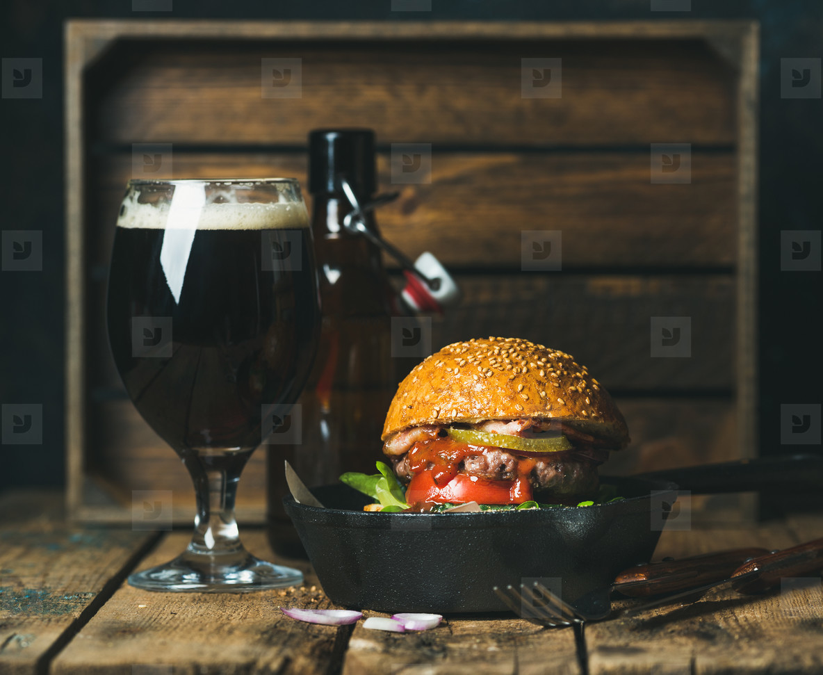 Beef burger with crispy bacon  fresh vegetables and dark beer