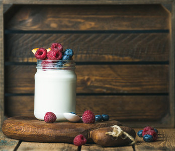 Glass jar of yogurt with fresh garden berries and peach