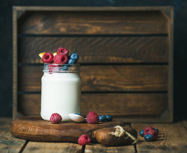 Glass jar of yogurt with berries and peach on board