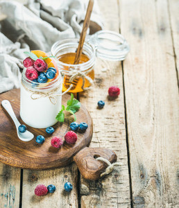 White yogurt in jar with fresh berries mint and honey
