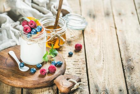 Glass jar of yogurt with fresh berries  mint and honey