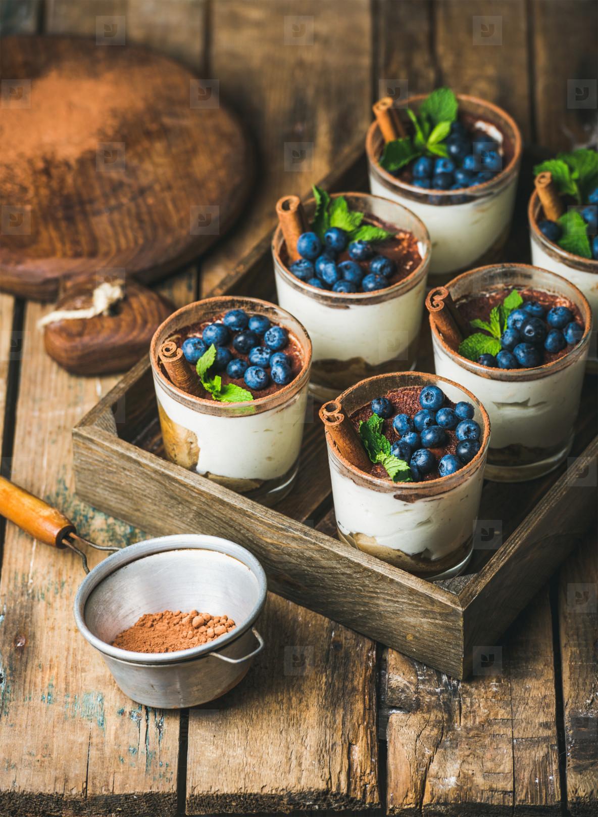 Homemade Tiramisu dessert in glasses with fresh berries and mint