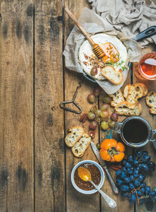 Camembert cheese  fruits  bread  honey  jam and wine  copy space