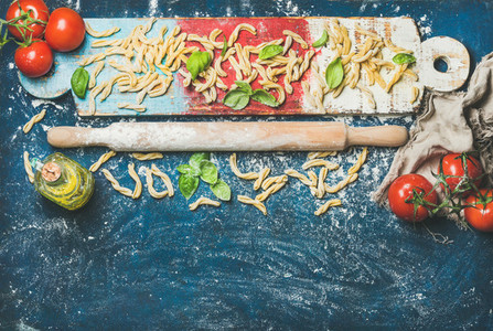 Fresh pasta casarecce  tomatoes  basil  olive oil on colorful board