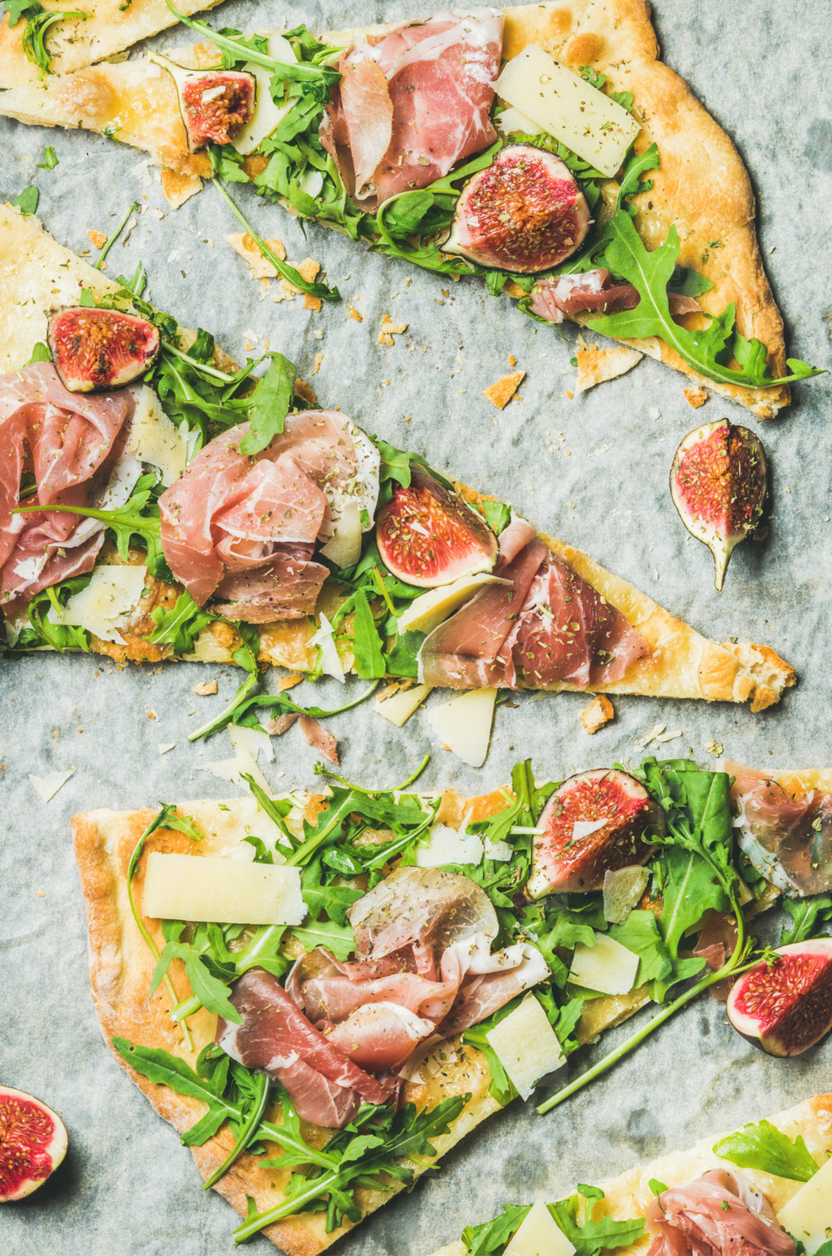 Pieces of fig  prosciutto  arugula and sage flatbread pizza