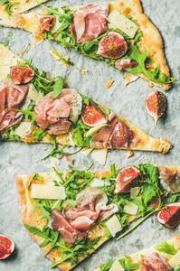 Pieces of fig  prosciutto  arugula and sage flatbread pizza