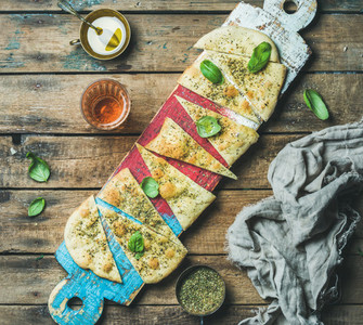 Focaccia with basil leaves olive oil wine on colorful board