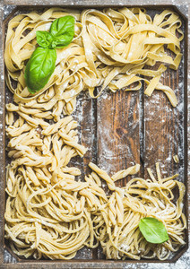 Various homemade uncooked Italian pasta in wooden tray
