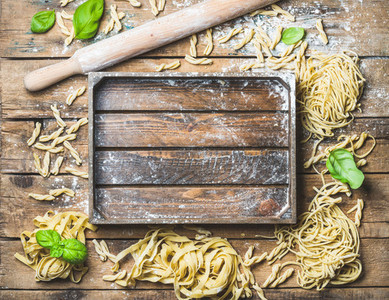Various homemade uncooked Italian pasta and wooden tray in center