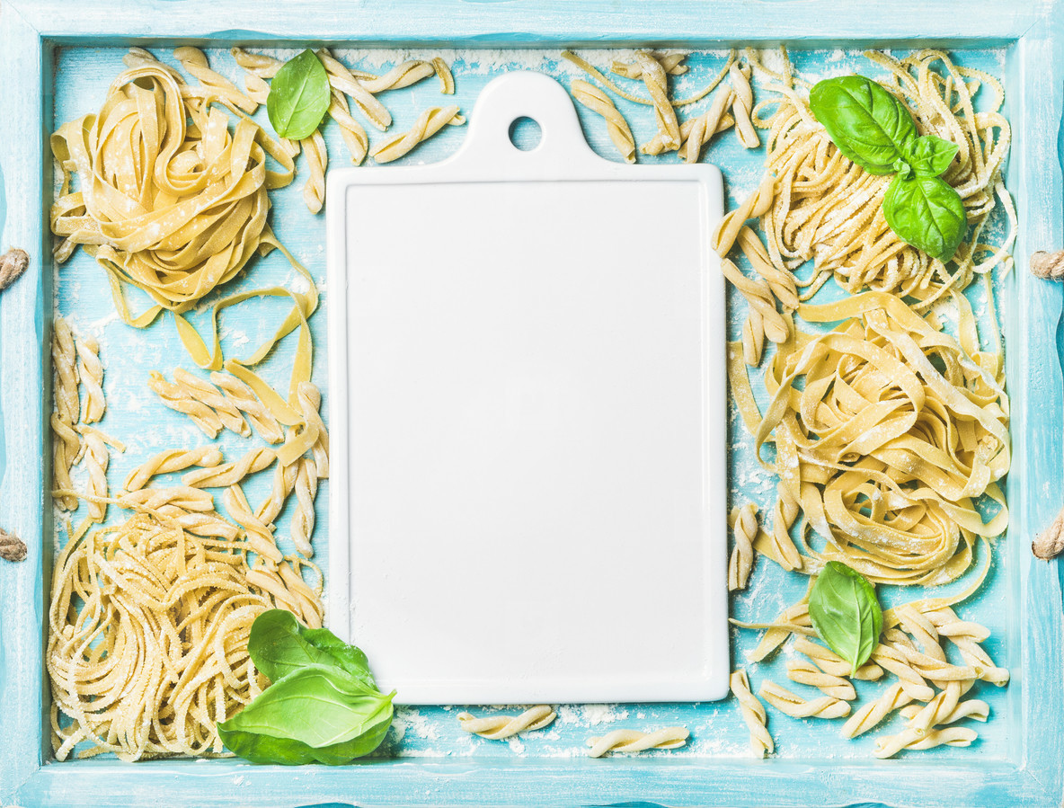 Various homemade fresh uncooked Italian pasta and white ceramic board