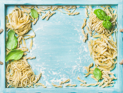Various homemade fresh uncooked Italian pasta in blue wooden tray