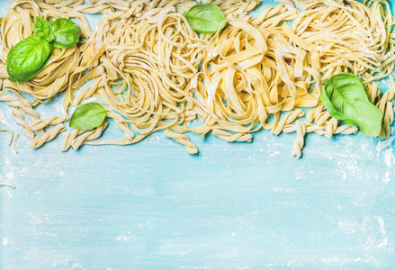 Different kinds of homemade fresh Italian pasta with green basil