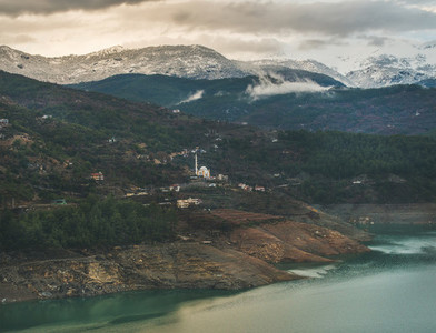 Dim Cay storage pond and mountains covered with snow  Alanya