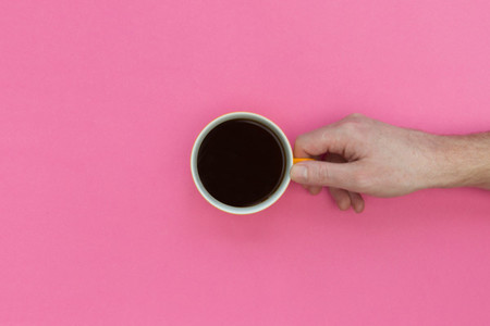 Holding coffee cup on pink