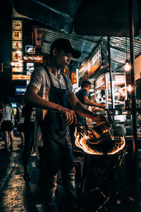 Man on street cooks with pan