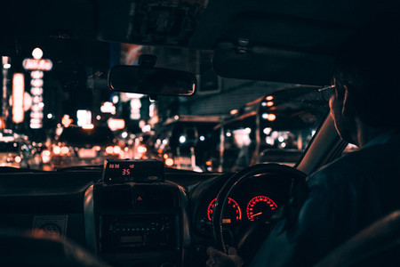 Man driving taxi cab at night