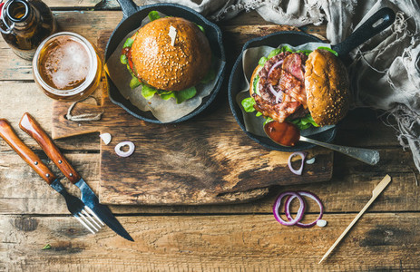 Beef burgers with crispy bacon  vegetables  glass of beer
