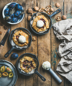 Plum and walnut crostata pie with ice cream scoops in pans
