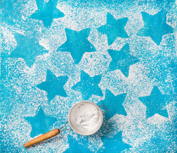 Sieve with sugar powder over bright blue background