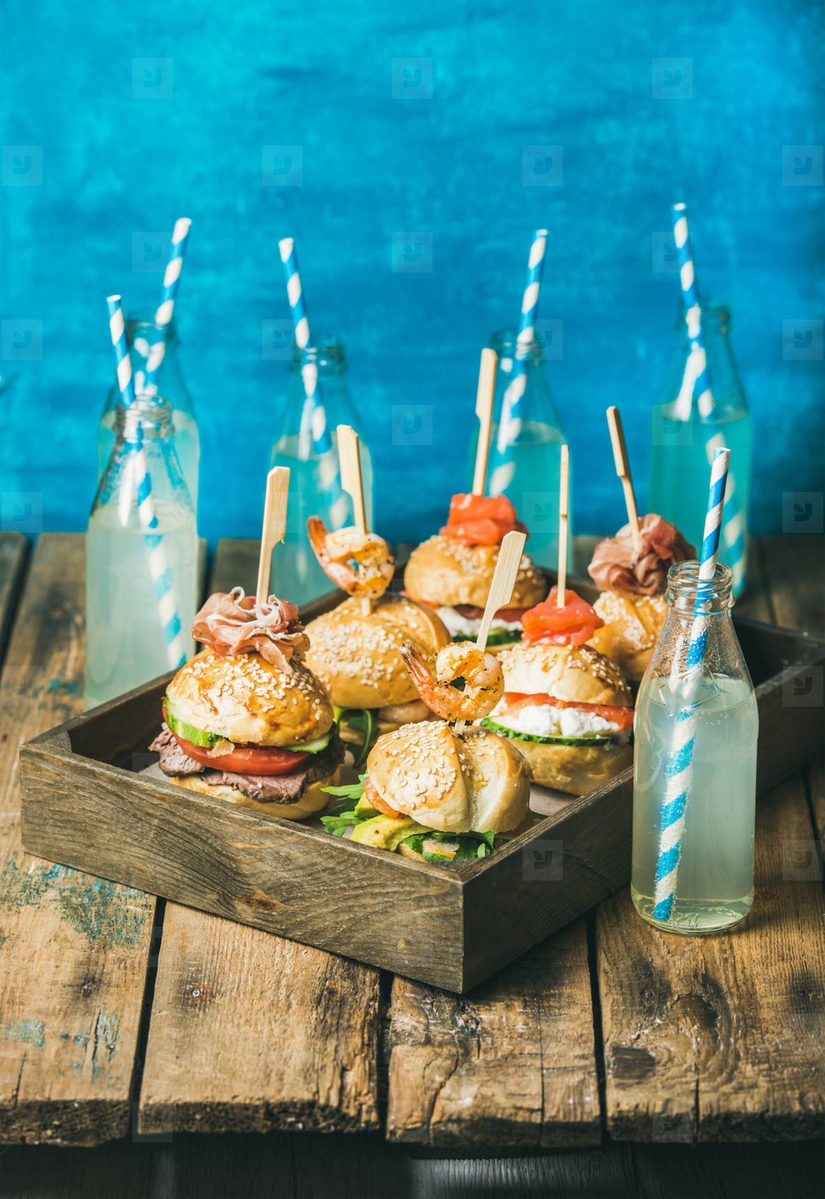 Different burgers with sticks in wooden tray and fresh lemonade
