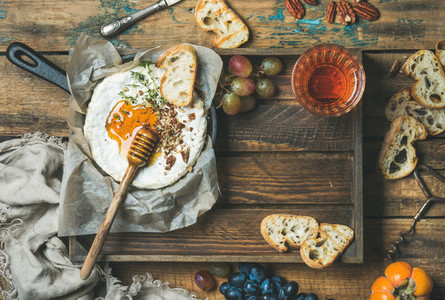 Homemade camembert with honey glass of rose wine and baguette