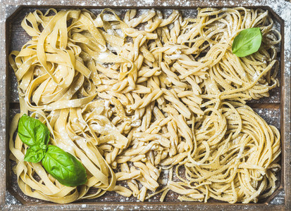 Uncooked Italian pasta in wooden tray with basil and flour