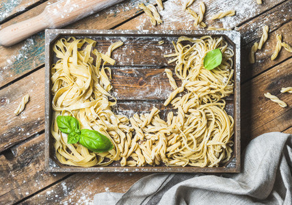 Various uncooked Italian pasta in wooden tray with basil leaves
