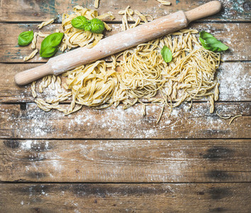 Various homemade fresh uncooked Italian pasta and plunger