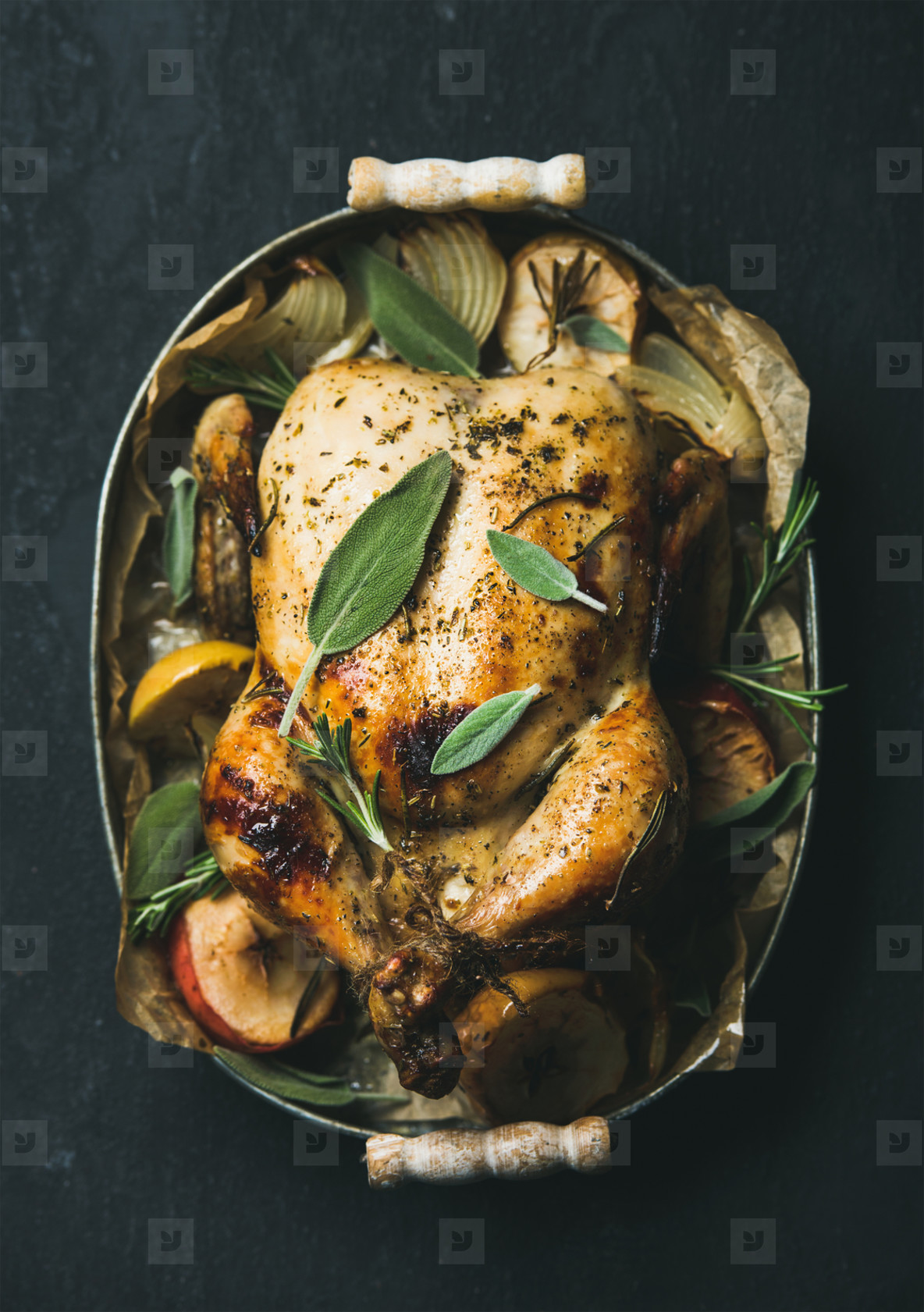 Oven roasted whole chicken with fresh sage leaves and apples