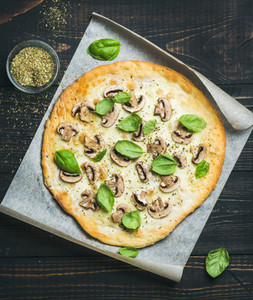 Homemade round mushroom pizza with basil and spices in glass