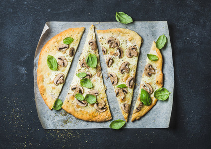 Homemade pizza with basil cut in slices on baking paper