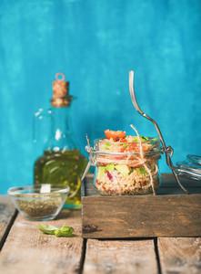Healthy homemade jar quinoa salad with tomatoes  avocado  fresh basil