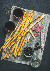 Italian Grissini  pork sausage  olives  red wine over dark background