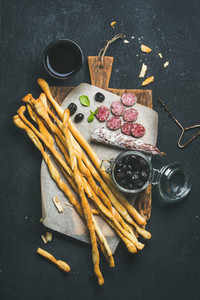 Wine and appetizers set with grissini  sausage  black olives