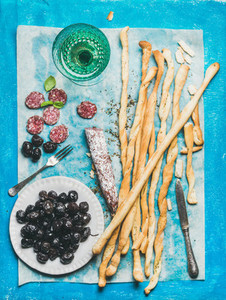 Grissini bread sticks  sausage  olives and white wine  blue background