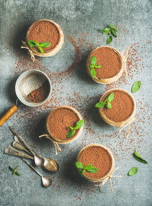 Homemade Tiramisu in individual glasses with mint copy space