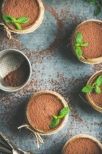 Homemade Italian dessert Tiramisu in glasses with mint copy space