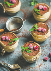 Homemade Tiramisu in individual glasses with frozen raspberries and mint