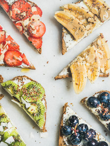Healthy breakfast toasts with cream cheese fruit nuts and seeds