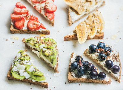 Healthy breakfast wholegrain bread toasts with cream cheese fruit seeds nuts