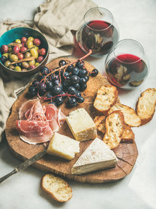 Cheese olives prosciutto baguette slices grapes and red wine
