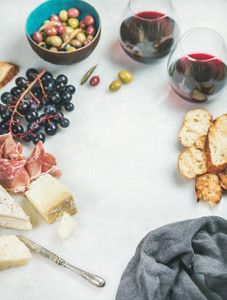 Red wine and snack set over grey background  copy space