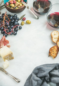 Red wine and snack set over grey marble background