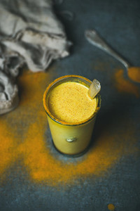 Golden milk with turmeric powder in glass selective focus