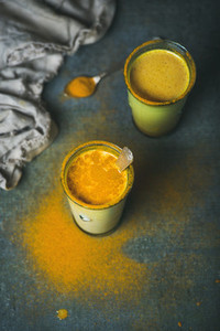Golden milk with turmeric powder in glasses  energy boosting drink