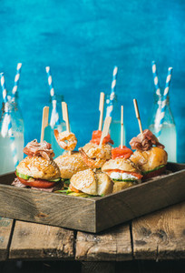 Different homemade burgers in wooden tray and lemonade in bottles