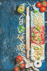 Fresh pasta casarecce  tomatoes  basil  olive oil on colorful board