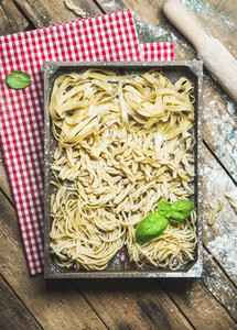Uncooked Italian pasta in wooden tray over rustic background